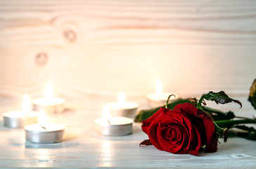 Red rose is among lighted candles on wooden white surface. The soft light of candles illuminates the flower.
