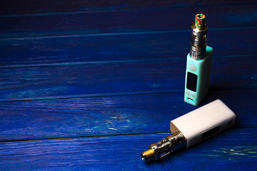 two e-cigarette (electronic cigarette, vape) on the wood backgro