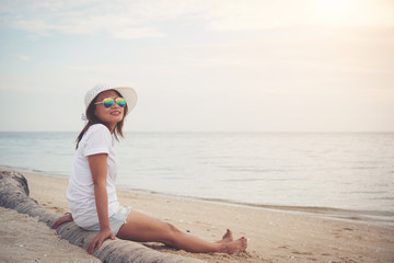 Young beautiful woman sitting on the beach wearing sunglasses. F
