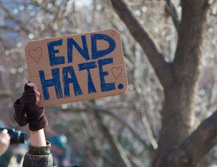 """Hand holding sign saying """"End Hate"""""""