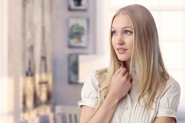 Beautiful young blonde woman daydreaming at home