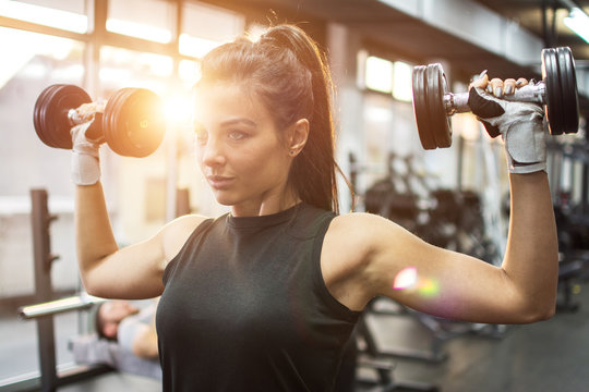 Beautiful young woman working out with dumbbells in gym.