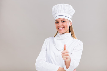 Portrait of beautiful female chef showing thumb up on gray background.