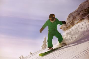 Fast snowboarder downhill in powder.
