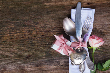 Valentines day dinner with vintage cutlery and fresh rose close up