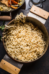 Pot with cooked asian noodles on rustic kitchen table, top view