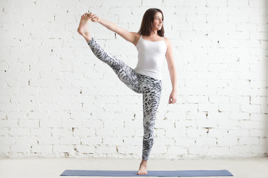 Attractive smiling woman practicing yoga, standing in Utthita Hasta Padangustasana exercise, Extended Hand to Big Toe pose, working out wearing sportswear, indoor full length, white studio background
