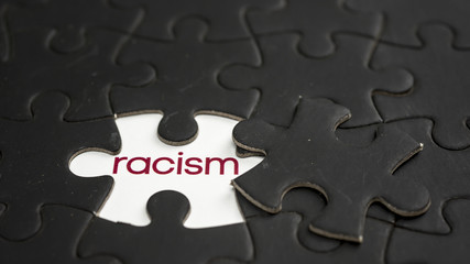 Word racism under jigsaw puzzle piece