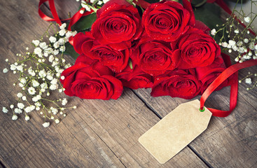 Blank card with red rose on a wooden background.