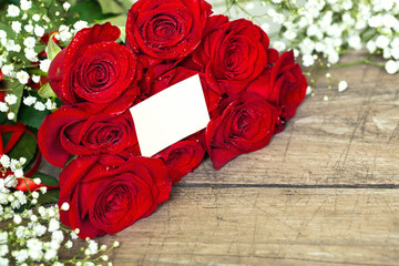 red roses on wooden table with blank white card.