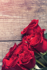 background with red roses over wooden table.