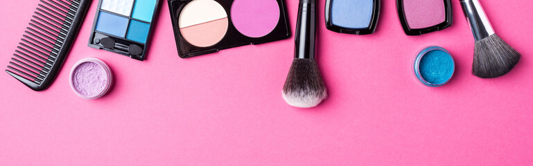 Makeup products on pink background. Top view