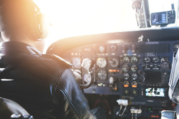 Adult airplane pilot wearing headset and outfit performing his job, sitting inside aircraft cockpit at steering control with modern dashboard. Bright sunshine penetrating into cabin through glass Fototapete