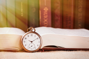 Vintage pocket clock on book against books background with beam of light