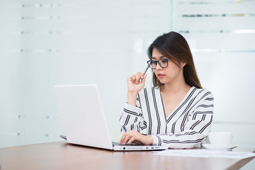 Beautiful young Asian woman thinking while working with laptop