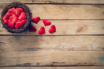 Red heart in the nest on wood background with space