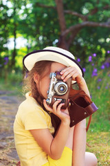 Cute little girl in retro outfit taking pictures with old camera