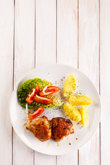 Grilled chicken thighs with boiled potatoes and vegetable salad