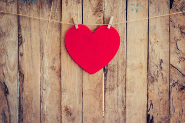 Red heart hanging on clothesline and rope with wooden background