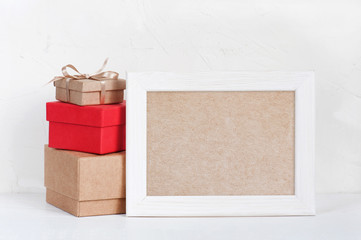 Empty frame and various gift boxes on the white table