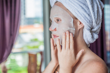 Young red-haired woman doing facial mask sheet