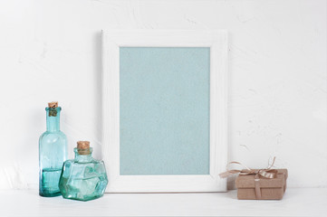 Empty wooden white frame, blue glass bottles and gift box