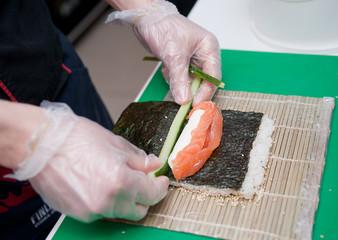 Sushi master preparing sushi rolls. On a sheet of nori puts slic