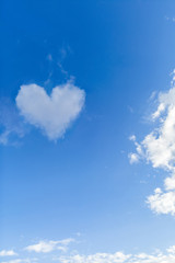 Sunny blue day with a heart shape cloud.