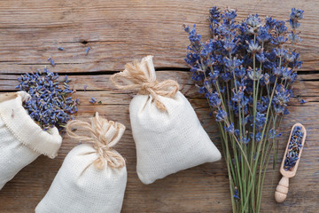 Dry lavender flowers and sachets on wooden background. Top view.