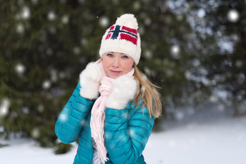 Young woman in knitted hat with Norwegian flag and scandinavian sweater. Winter landscape
