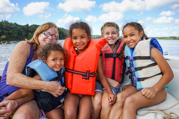 Family in Life jackets on a boat on a lake