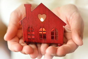 Warm and cozy miniature house in female hands. Care and love.