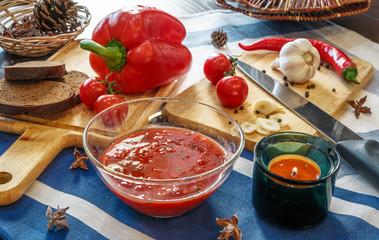 Процесс приготовления томатного соуса аджики и овощи на кухонном столе