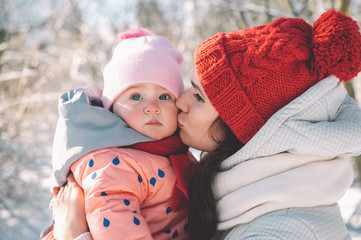 Mom kissing her baby in winter park