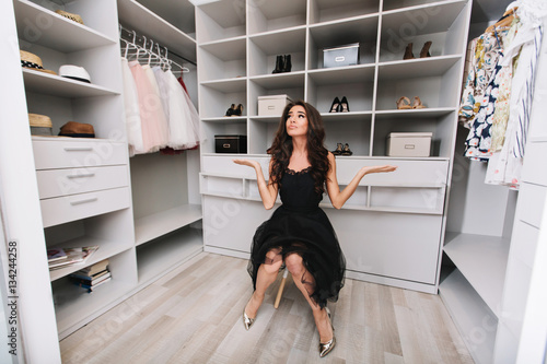 2a3bf9f9bb298 Young brunette woman sitting in a huge dressing room thinks over the choice  of clothes, she is dressed stylish black outfit and silver shoes, ...