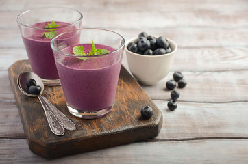 Blueberry and banana smoothie with oatmeal on the rustic wooden table, selective focus, horizontal, copy space
