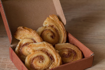 Cinnamon rolls buns in gift box on wood. Christmas surprise.