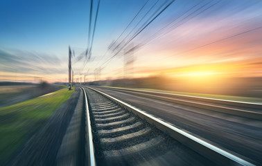 Railroad in motion at sunset. Railway station with motion blur effect against colorful sky, Industrial concept background. Railroad travel, railway tourism. Blurred railway. Transportation. Vintage