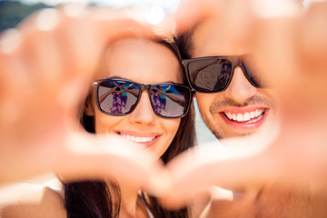Close up of smiling  family in glasses making heart with fingers