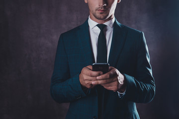 Close up of serious young successful man typing message on phone