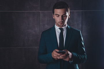 Young concentrated businessman chatting on smartphone on gray ba