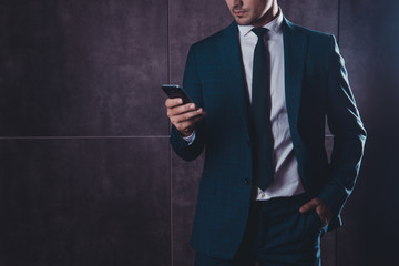 Close up of businessman in black suit using smartphone on gray b