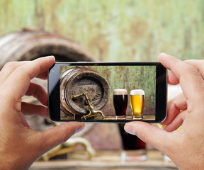 Taking photo of glasses of beer by smartphone.
