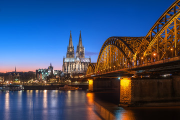 Cologne Cathedral and Hohenzollern Bridge at nighttime.