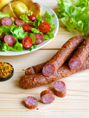 Sausage with vegateble salad on a wooden board