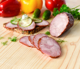 Smoked sausage with herbs on a wooden board