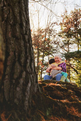Grandmother and granddaughter sitting in forest hugging