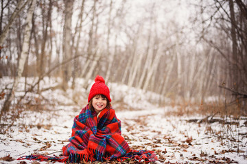 Girl sitting in snow wrapped in a blanket