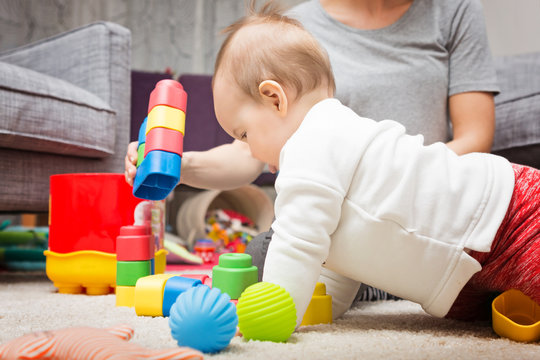 Nine months old baby girl playing with her toys on the floor and