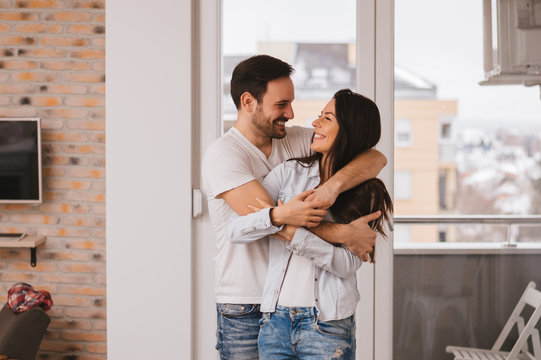 Beautiful young couple hugging in their new appartment.